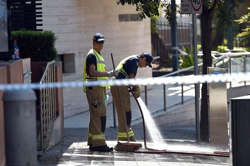 Firemen on Saturday hosing down the scene where a 15-year-old gunman had shot dead a civilian police employee the previous day before being gunned down by police in Sydney.
