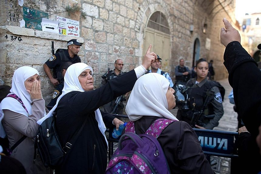 Palestinian women shouting slogans during a demonstration in the Muslim quarter of Jerusalem's Old City yesterday.