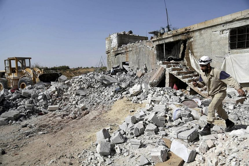 A damaged building next to a site hit by what activists said were air strikes carried out by the Russian air force in the Syrian town of Ehsim.