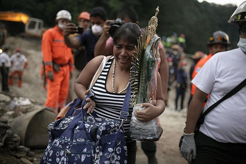 A woman with a religious statue and belongings evacuating from a mudslide-hit area in Santa Catarina Pinula. Hopes of finding more survivors are fading.
