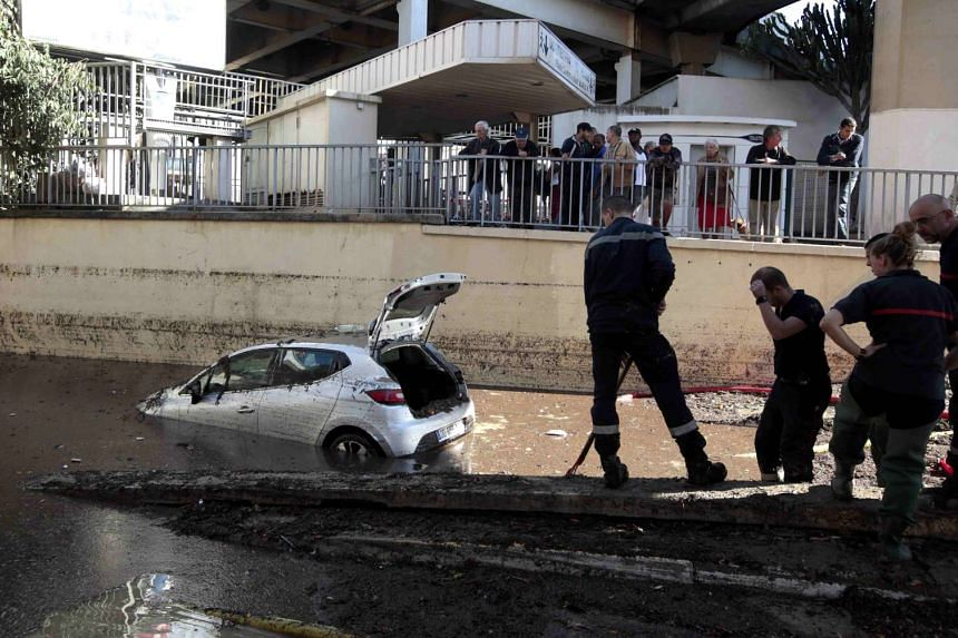 French fireman work near an abandoned car stuck in muddy waters near an underpass after flooding caused by torrential rain in Cannes on Oct 4, 2015.