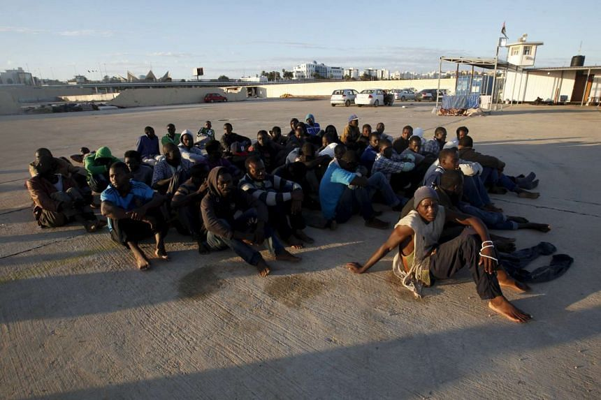 Migrants who attempted to flee the Libyan coast to head to Europe sit after they were detained at the Libyan naval base in the coastal city of Tripoli on Sept 29, 2015.