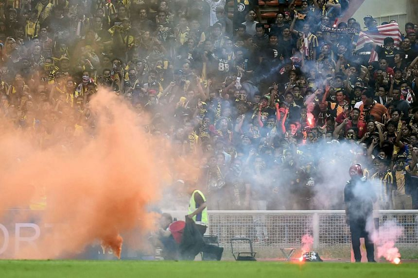 Flares burn on the pitch after Malaysian fans threw them there during their national team's 2018 FIFA World Cup qualifying football match against Saudi Arabia in Shah Alam on Sept 8, 2015.