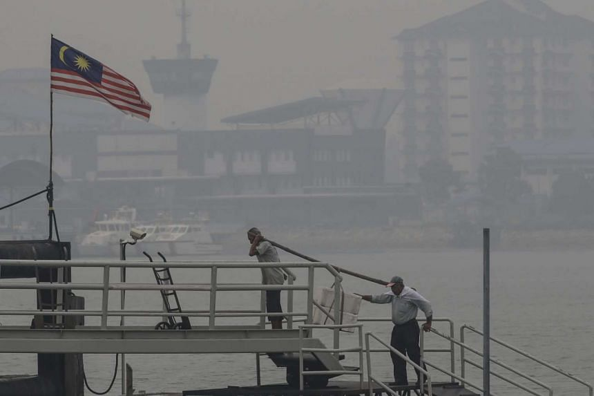 Workers moving cargo amid the haze in Port Klang, outside Kuala Lumpur on Oct 5, 2015.