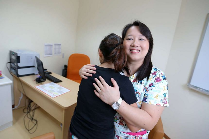 Mrs Regina Lua Ubana (right), an advanced practice nurse in the Department of Child & Adolescent Psychiatry (Sunrise Wing/Child Guidance Clinic), Institute of Mental Health, hugs a patient during a counselling session.