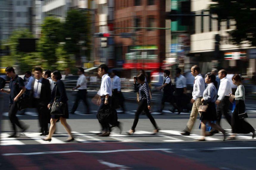 Pedestrians cross a road in Tokyo, Japan, on Sept 28, 2015.