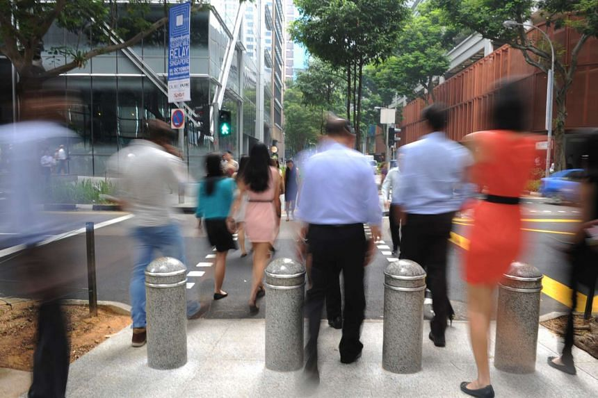 Pedestrians crossing the road at Raffles Place.