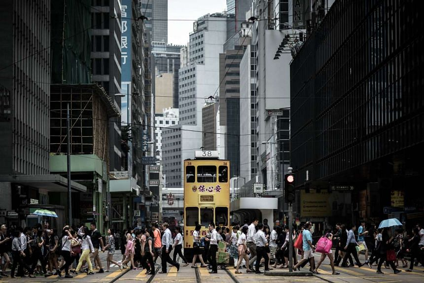 In this photograph taken on Aug 25, 2015, pedestrians walk past a tramway in Hong Kong.
