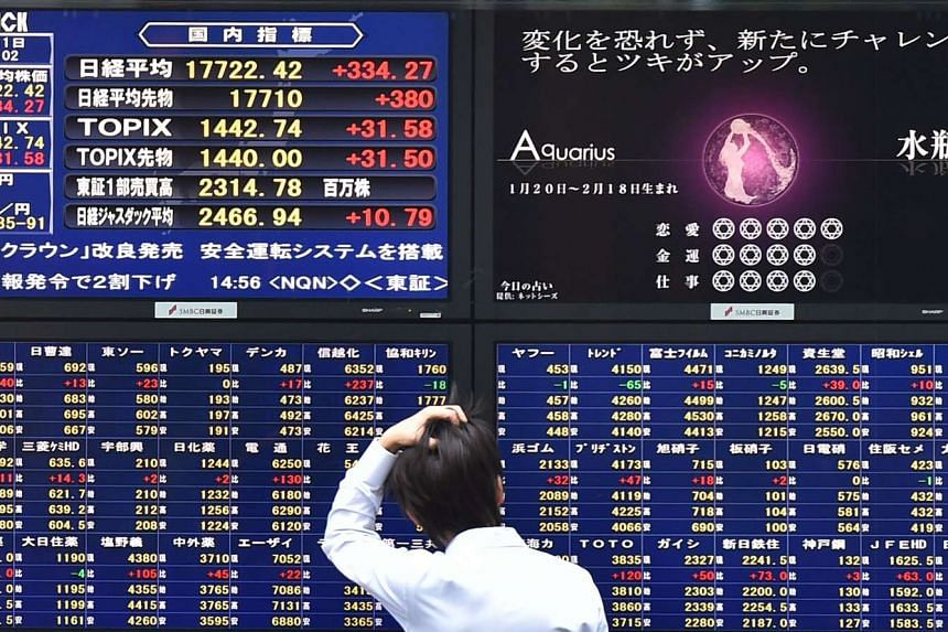 A man looks at an electronic board showing the numbers (left) on the Nikkei 225 at the Tokyo Stock Exchange in Tokyo on Oct 1, 2015.