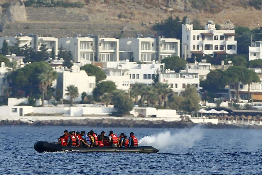 Smoke rises from the motor of a dinghy as it is paddled by migrants to reach the Greek Island of Kos after leaving Bodrum, Turkey, in the hopes of crossing the Mediterrean Sea, in this Sept 20, 2015, file photo.