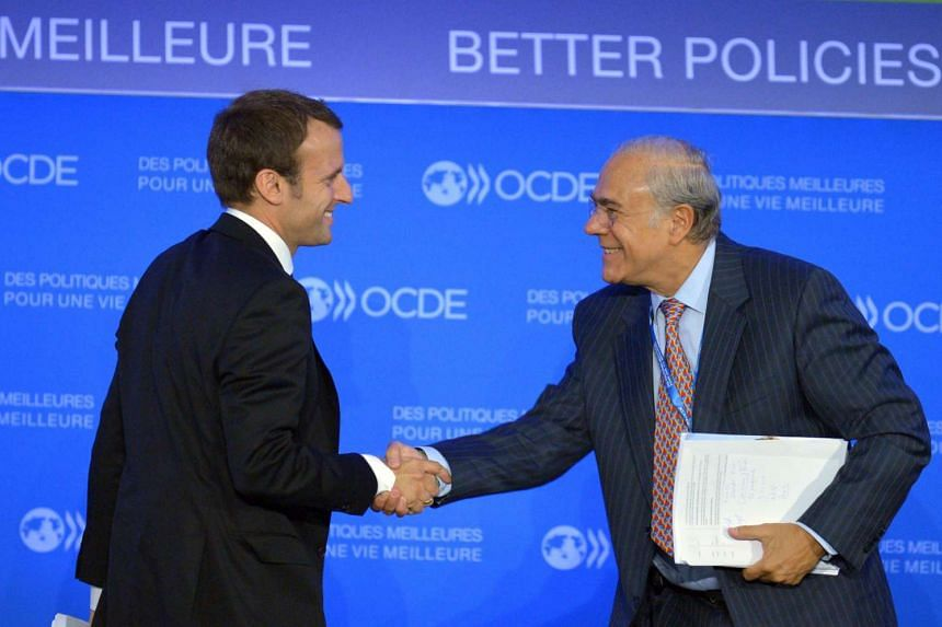 A file picture of French Economy Minister Emmanuel Macron (L) shaking hands with OECD Secretary General Angel Gurria (R) after attending a talk at the OECD headquarters in Paris on September 18, 2015. PHOTO: AFP