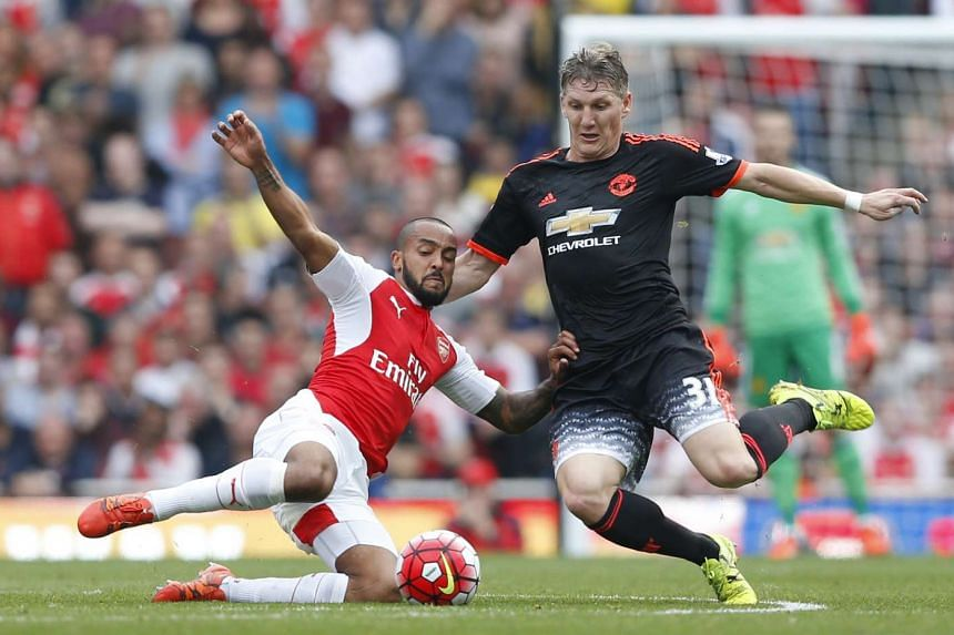 Arsenal's Theo Walcott in action with Manchester United's Bastian Schweinsteiger