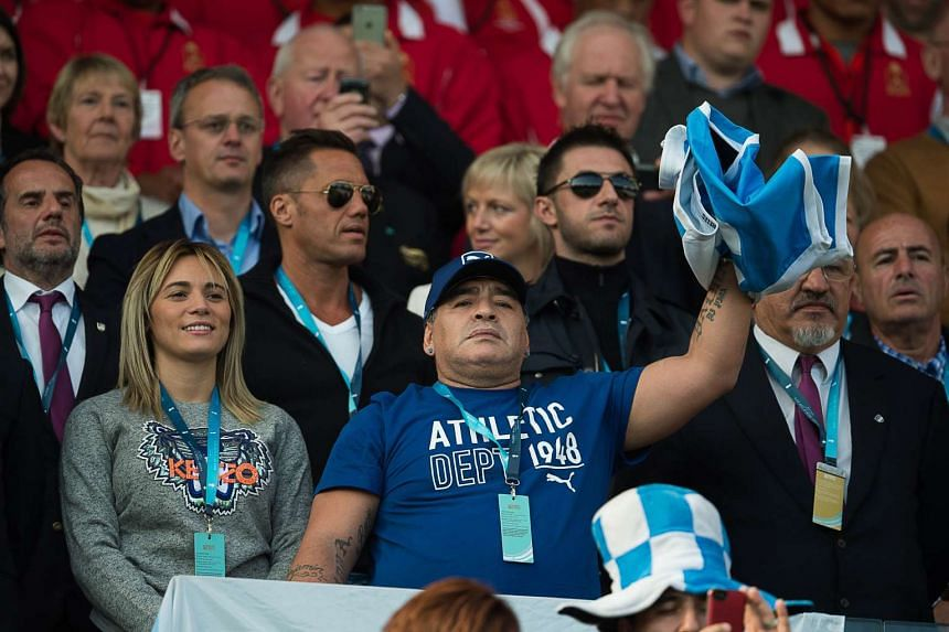 Former Argentina football international Diego Maradona (centre) waves a flag at the 2015 Rugby World Cup match between Argentina and Tonga at Leicester City Stadium on Sunday.