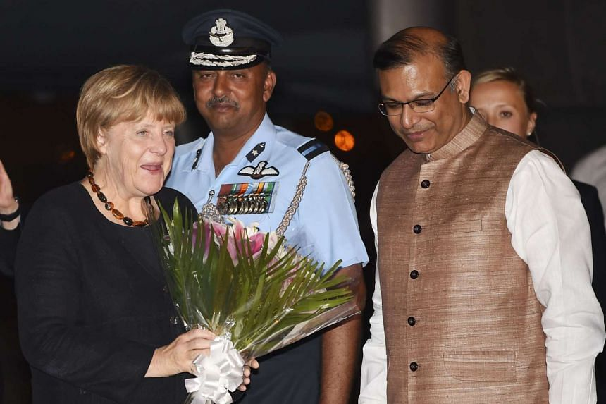 German Chancellor Angel Merkel smiles and holds a bunch of flowers as she greets Indian officials after arriving at the airport in New Delhi on Sunday for a two-day visit to India.