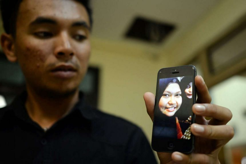 A relative of a passenger onboard the missing Aviastar plane shows her picture on his mobile phone at a crisis centre in Hasanuddin International Airport in South Sulawesi.