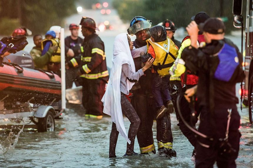 A fireman handing a boy over to his mother after they were stranded by floodwaters in Columbia, South Carolina, yesterday. The state has been experiencing record rainfall, made worse by high tides.