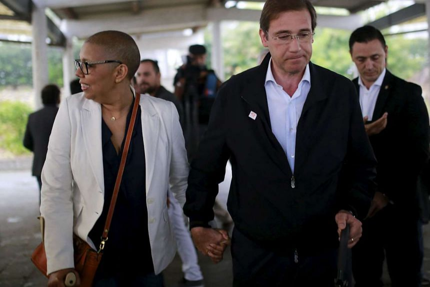 Portugal's Prime Minister Pedro Passos Coelho leaving the polling station with his wife after casting their votes in Massama.