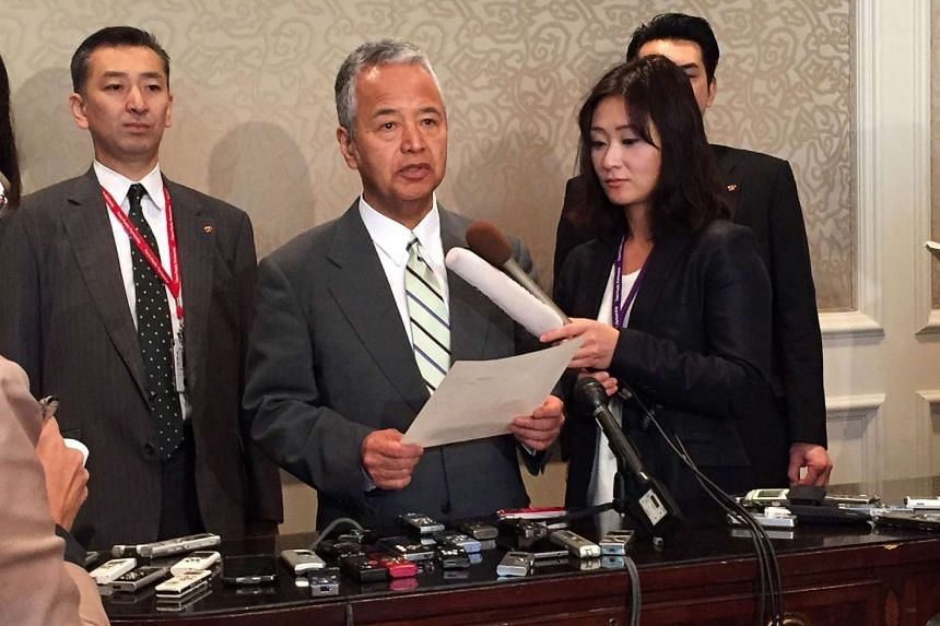 Japan's Economy Minister Akira Amari (centre) speaking to the media during a break in TPP talks on Oct 3, 2015.