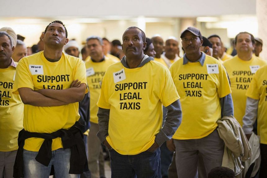 Uber protesters that could not fit into city council to watch the debate on taxi regulations from the foyer of city hall in Toronto, Sept 30, 2015.
