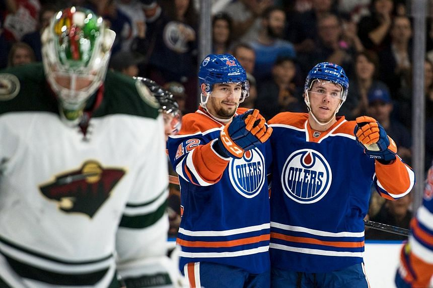 Edmonton Oilers' Anton Slepyshev (42) and Connor Mcdavid (97) celebrating after a goal during the first period of their NHL hockey game against the Minnesota Wild on Sept 26, 2015.
