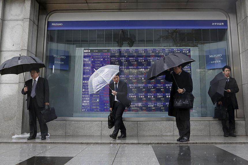 Pedestrians holding umbrellas stand in front of a stock index board showing various stock prices outside a brokerage in Tokyo in this Apr 3, 2013, file photo.