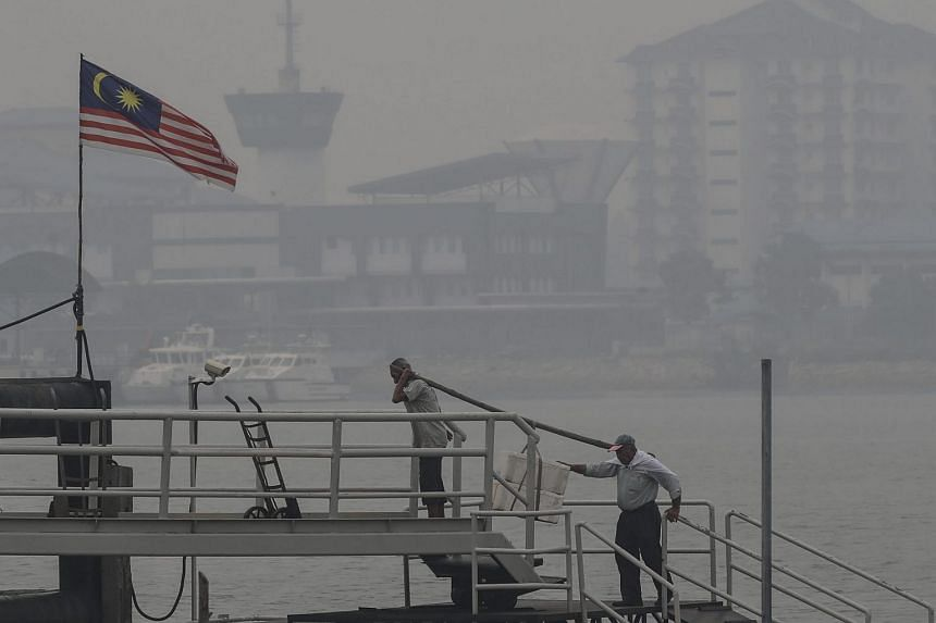 Workers shrouded by haze in Port Klang, outside Kuala Lumpur, Malaysia, Oct 5, 2015.