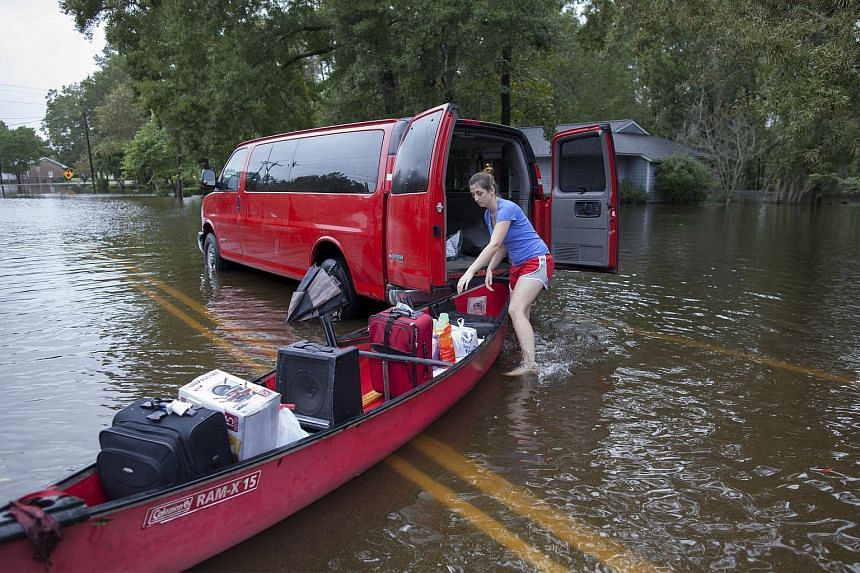 A woman using a canoe to evacuate her home on Long Avenue in Conway, South Carolina, on Oct 5.