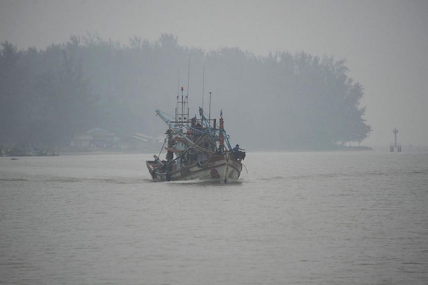 A fishing boat sailing on the Narathiwat river through haze in Narathiwat, southern Thailand, on Oct 5, 2015.