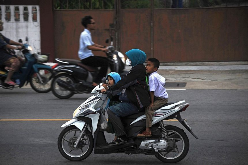 A woman wearing a face mask as she rides a motorcycle with children through haze in Narathiwat, southern Thailand, on Oct 5, 2015.