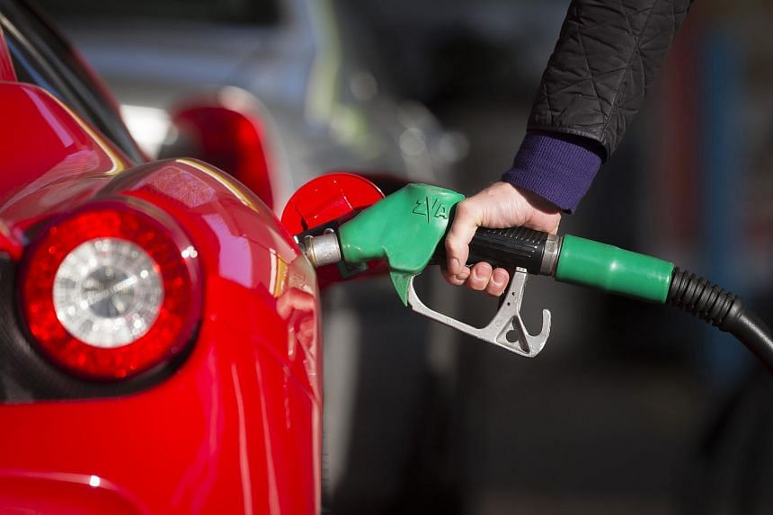 A driver refuelling his car with petrol at an Esso gas station.