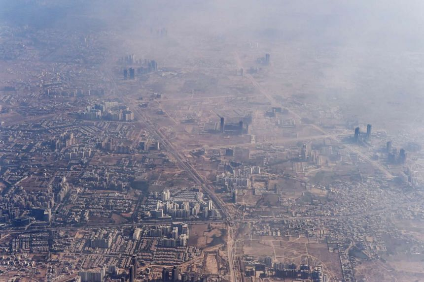 In this photograph taken on Nov 25, 2014, smog envelops buildings on the outskirts of the Indian capital New Delhi.