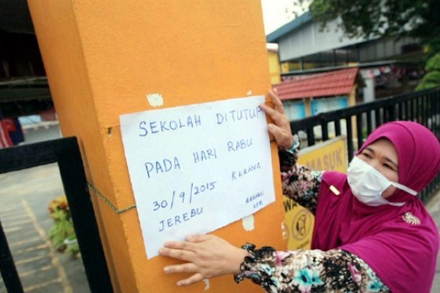 A teacher in Johor Bahru, Malaysia, puts up a sign to inform parents and students of the school closure due to the unhealthy levels of haze.