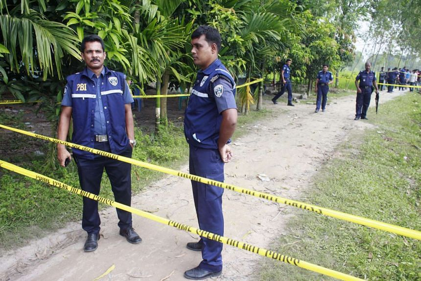 Bangladeshi police officials stand guard in Rangpur, at the site where a Japanese citizen was shot to death, on Oct 4, 2015.