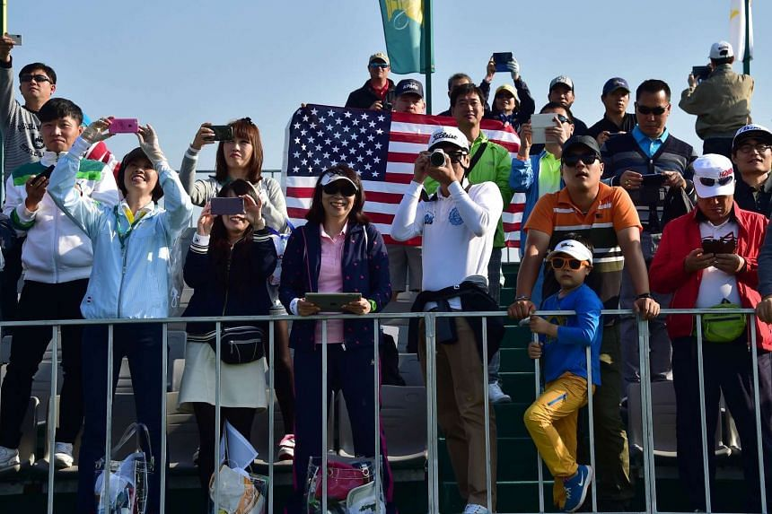 South Korean visitors take pictures as the US Team players warm up on the practice ground ahead of the 2015 Presidents Cup on Oct 6. 2015.