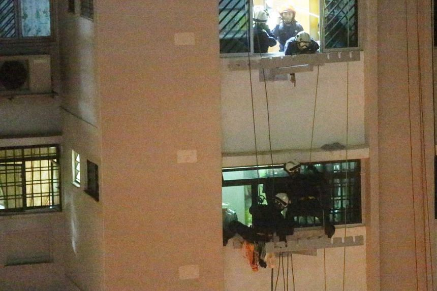 SCDF officers making their way down to the seventh-floor unit from the unit above, ending a two-hour confrontation with a 51-year-old man who threatened to kill his landlady, on Oct 5, 2015.