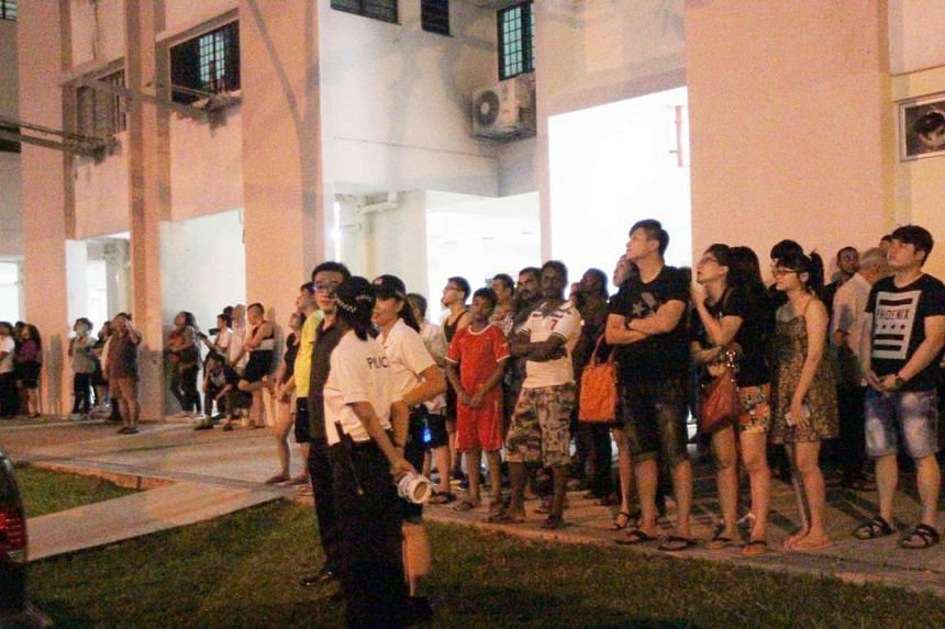 Residents of St George's Lane watching the confrontation between a man waving a kitchen knife and riot police and SCDF officers.