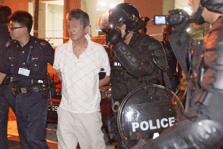 A 51-year-old man (in white) was arrested on Monday night after a two-hour confrontation with riot police and SCDF officers, during which he waved a knife at his landlady and threatened to kill her.