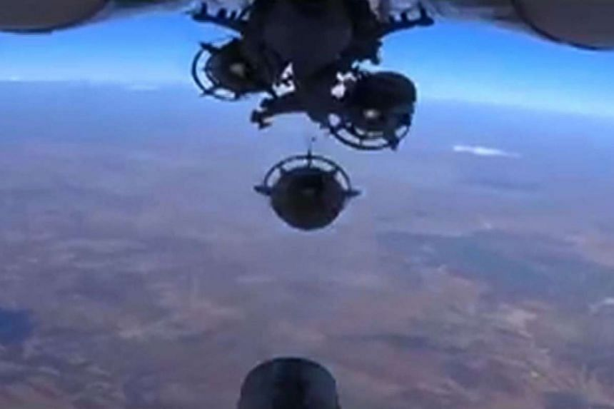 An image grab made from a video reportedly shows a Russian aircraft dropping bombs against Islamic State in Iraq and Syria (ISIS) positions at an undisclosed location in Syria.