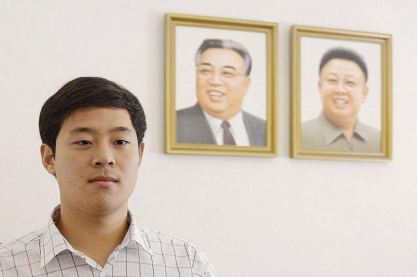 Mr Joo Won Moon, a South Korean with permanent US residency, in front of portraits of North Korea's former leaders Kim Jong Il (right) and Kim Il Sung during a press conference in Pyongyang on Sept 25.