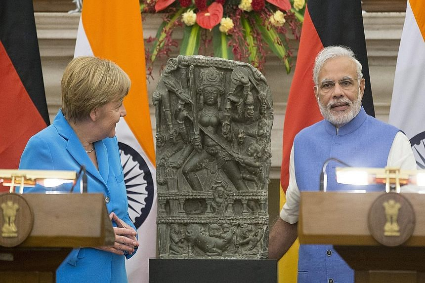 Dr Merkel and Mr Modi at a joint news conference in New Delhi yesterday. Behind them is a statue of Hindu goddess Durga, which was returned to India by the Linden Museum of Stuttgart during Dr Merkel's visit.