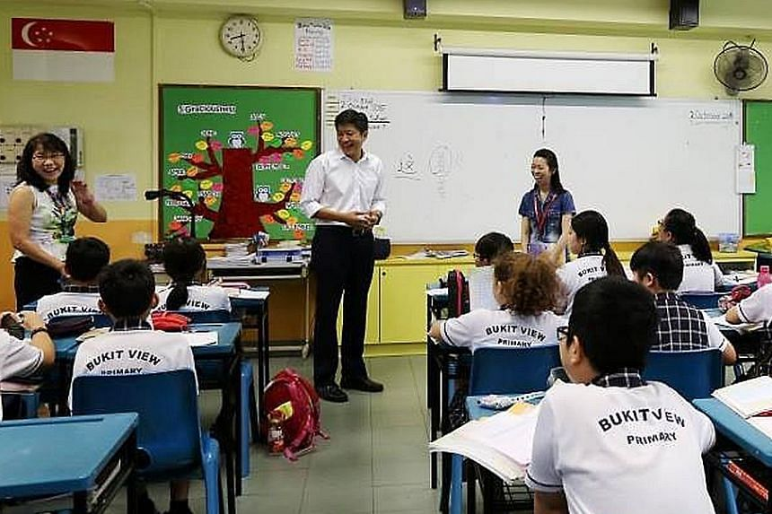 (Above) Mr Ng Chee Meng visiting a class during a Chinese lesson at Bukit View Primary School last Friday. (Right) Mr Ong Ye Kung with pupils from CHIJ Our Lady Queen of Peace at the launch of Clean and Green Week in Bukit Panjang last Saturday.
