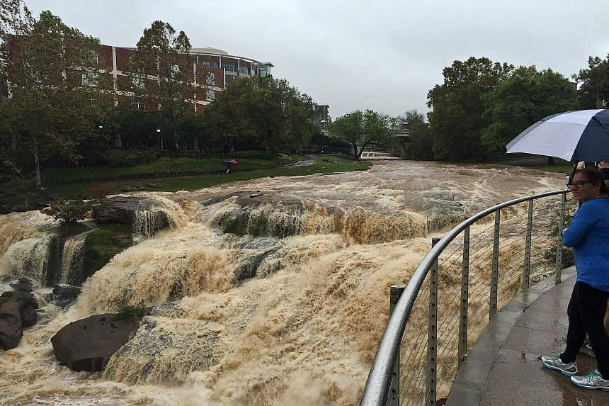 Flood waters in downtown Greenville, South Carolina, after record rainfall which left large areas submerged. At least eight people have died since the wild weather hit the Carolinas last Thursday. US President Barack Obama has declared a state of eme