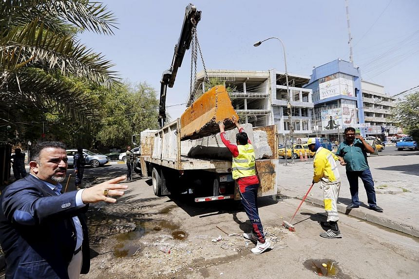 Workers removing a concrete barrier on a street in central Baghdad on Aug 30. The Iraqi authorities unblocked a street in Baghdad's Karrada district, near the Green Zone, on Sunday, following a decision by the prime minister to improve access in the