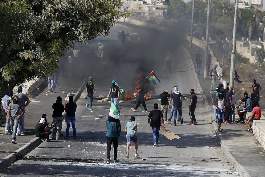 Palestinians gathering near a burning barricade during clashes with Israeli security forces in the East Jerusalem neighbourhood of Issawiya on Sunday.