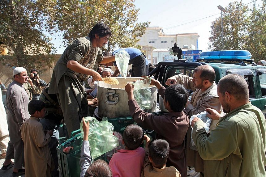 Residents receiving food distributed by police in the city of Kunduz, Afghanistan, on Sunday. Afghan security forces said yesterday they had reclaimed most of the city from the Taleban, allowing residents to leave their homes to buy food for the firs