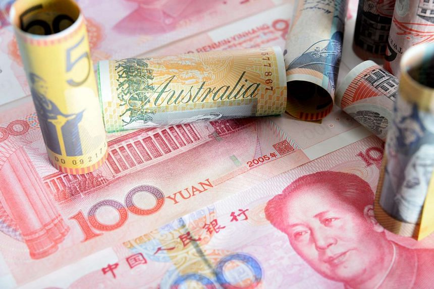 Australian and Chinese banknotes. Australia left interest rates unchanged on Tuesday (Oct 6) as the local dollar recorded the biggest drop among major currencies last quarter, cushioning the impact of a weaker outlook in China.