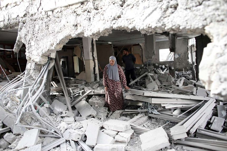 A Palestinian woman walks amid the rubble of a house after Israeli security forces demolished the homes of two Palestinians behind attacks in the Palestinian neighborhood of Jabal Mukaber in east Jerusalem, on Oct 6, 2015.