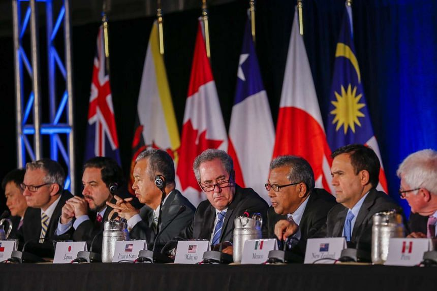 United States Trade Representative Michael Froman (centre) is flanked by international counterparts during the closing press conference after an agreement was reached by twelve Trans-Pacific Partnership (TPP) member countries, in Atlanta, Georgia, US