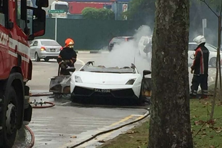 SCDF personnel putting out the fire in the Lamborghini.