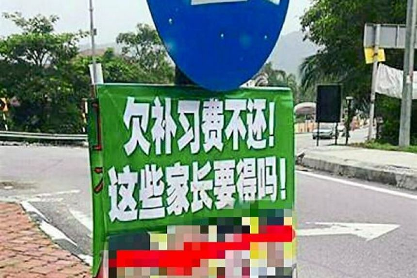 "One of the banners seen in the Sungai Long and Cheras areas in Malaysia's state of Selangor. The Mandarin words, above the photos of four children, read: ""Owe Tuition Fees but refuse to pay up! Do they deserve such parents!"""